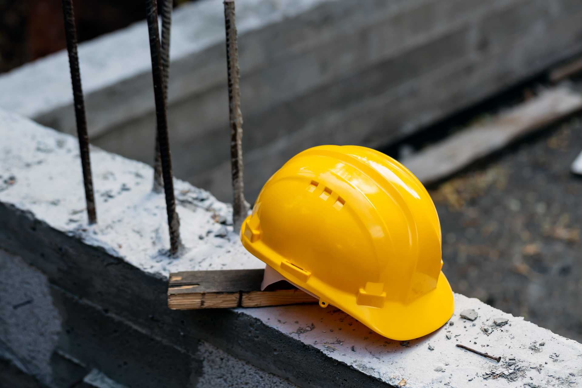 Construction hard hat safety tools equipment for workers in construction site for engineering protection head standard on building construction background. Yellow helmet.