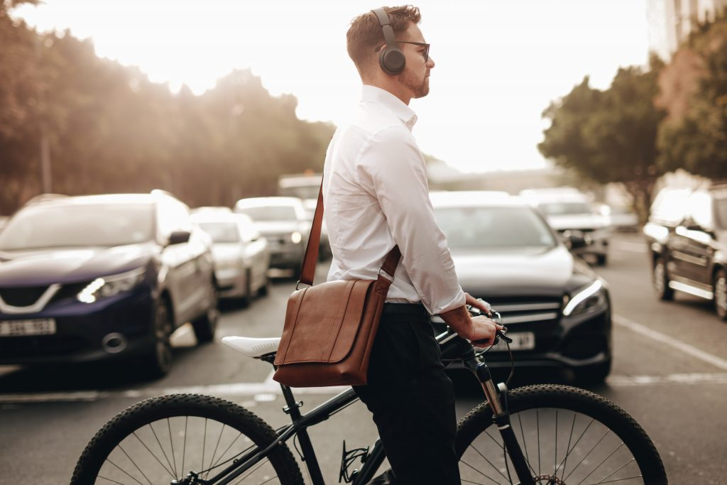 Businessman walking on road holding his bicycle crossing the road. Man wearing office bag and wireless headphones going to office holding his bike.